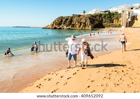 ALBUFEIRA, PORTUGAL - OCTOBER 22, 2015: A happy senior couple is walking together on the beach of Albufeira in Portugal while others are (sun)bathing.  - stock photo