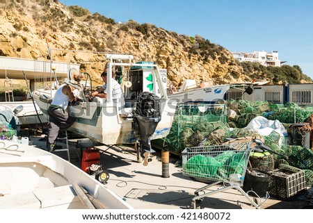 Albufeira, Portugal - October 22, 2015: An old fisher boat is being repaired by two men in a shipyard in Albufeira, Portugal. - stock photo