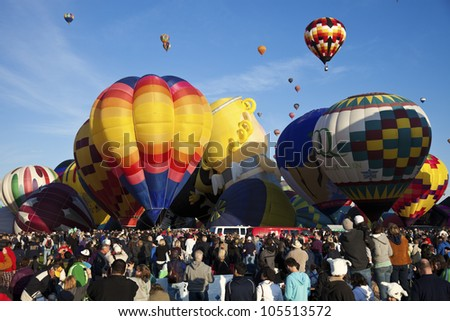 ALBUQUERQUE, NM - OCTOBER 02: Hot Air Balloon Fiesta in Albuquerque, New Mexico. Crowd of the visitors observing the ascending balloons during clear fall morning on October 2, 2011. - stock photo
