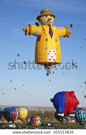 ALBUQUERQUE, NM - OCTOBER 02: Hot Air Balloon Fiesta in Albuquerque, New Mexico. Crowd of the visitors observing the ascending balloons on October 2, 2011. Smiling Strawman baloon in the center. - stock photo