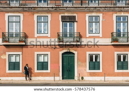ALCANTARA, LISBON, PORTUGAL - FEBRUARY 6: woman is waiting in front of the old  pink residential building in Alcantara area, Lisbon, Portugal on February 6, 2017.