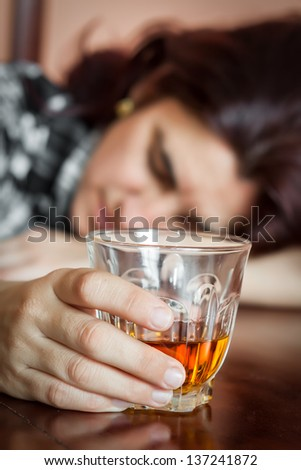 Alcohol abuse : Drunk hispanic woman holding a drink and sleeping on a table