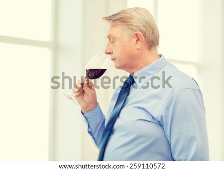 alcohol and beverage concept - older man smelling red wine - stock photo
