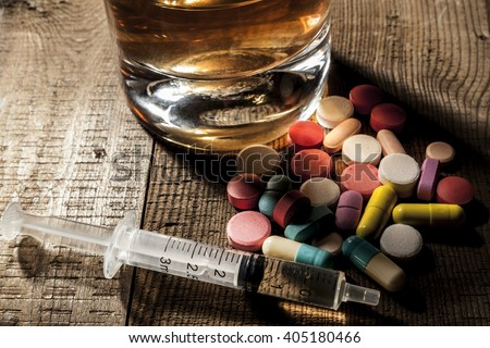 Alcohol and pills on table with shadow - stock photo