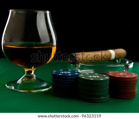 alcohol, chips and cigar on a black background - stock photo