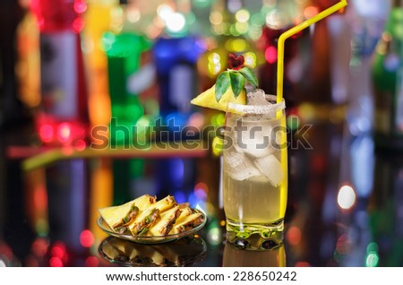 Alcohol cocktail with pineapple on the bar on the blur background.