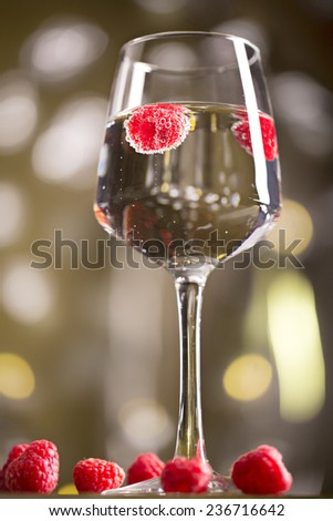 Alcohol cocktail with raspberry on the magenta blurred background - stock photo