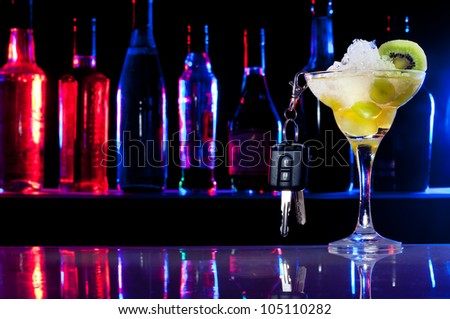 Alcohol drink in cocktail glass and car keys hanging from it - stock photo
