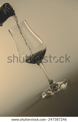 alcohol drink pouring into glass isolated on white background - stock photo