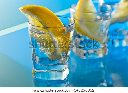 alcohol drink with lemon on a glass table - stock photo
