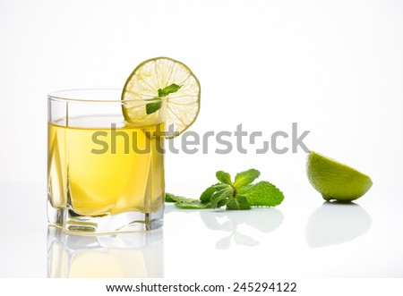 Alcohol in glass with slice of lime - stock photo