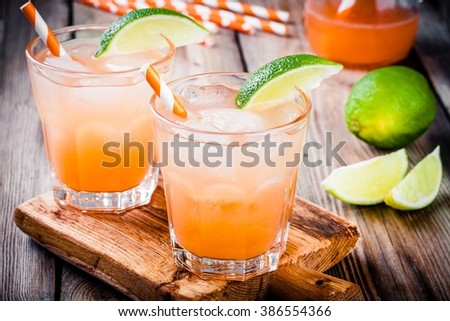 Alcohol tequila sunrise cocktail with ice and lime - stock photo