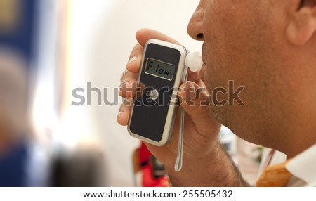 alcohol testing, man blowing in breathalyzer - stock photo