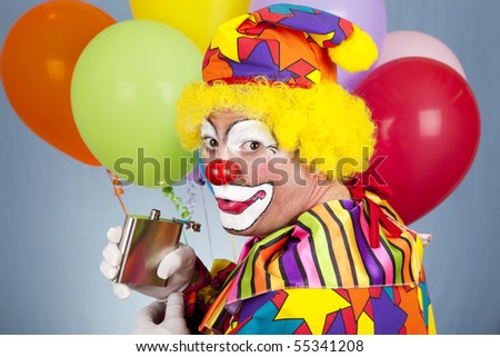 Alcoholic clown sneaks a drink from his flask. - stock photo