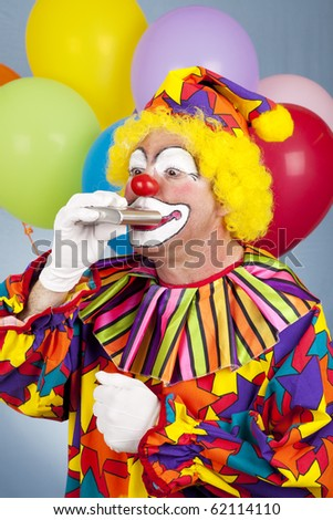 Alcoholic clown takes a drink from his flask. - stock photo