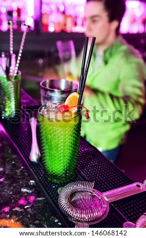 Alcoholic cocktail and bar inventory at nightclub. Barman professional making cocktail drinks in background soft focus - stock photo