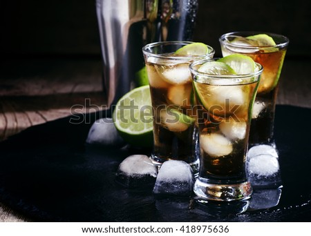 Alcoholic cocktail spiced rum with cola, lime and ice cubes, shaker, black background, selective focus - stock photo