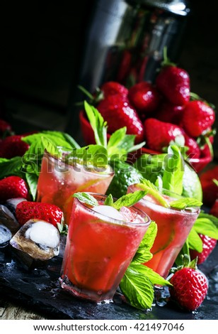 Alcoholic cocktail strawberry mojito with white rum, syrup, soda, lime, mint and ice, black background, selective focus - stock photo