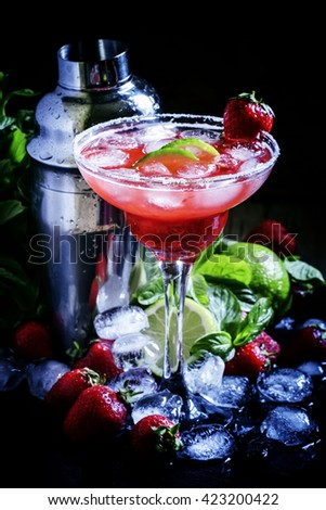 Alcoholic cocktail with strawberry, lime and ice in the glass, decorated with sugar, black background, selective focus on the contents of the glass - stock photo