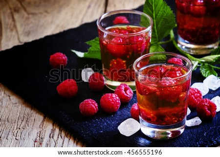Alcoholic cocktail with strong alcohol, syrup and fresh raspberries, black background, selective focus - stock photo
