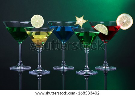 Alcoholic cocktails in martini glasses on dark green background - stock photo