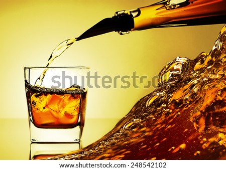 alcoholic drink  being poured into a glass with ice - stock photo