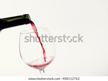 Alcoholic drink. Red wine pouring - stock photo