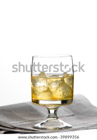 Alcoholic drink with ice and newspapers - stock photo