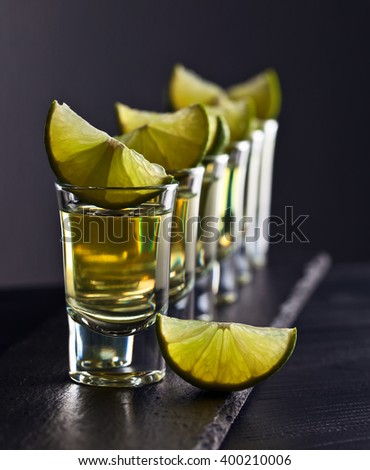 alcoholic drink with lime on dark background - stock photo