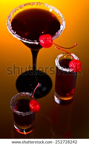 alcoholic drinks with sweet cherries on glass table - stock photo