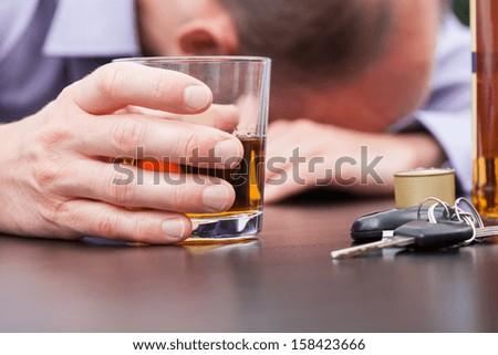 Alcoholic sleeping on the table with car keys - stock photo