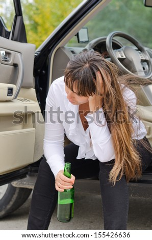 Alcoholic woman driver stopping for a drink of alcohol from a a bottle sitting on the sill in the open door of her car with her head resting on her hand - stock photo