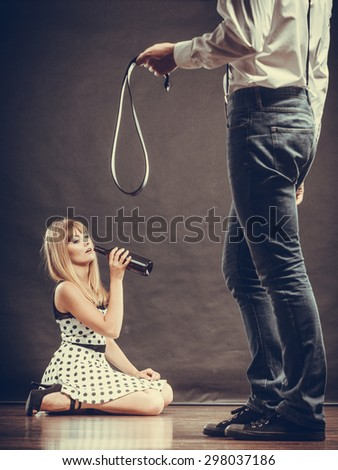 Alcoholism and violence problem. Man beating his wife with belt. Woman addicted to alcohol is victim of domestic abuse - stock photo