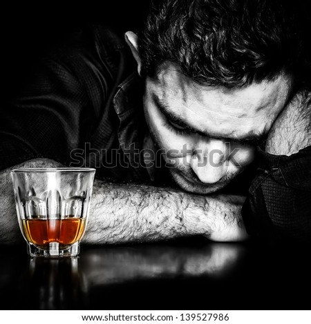 Alcoholism : Dark portrait of a lonely and desperate drunk hispanic man - stock photo