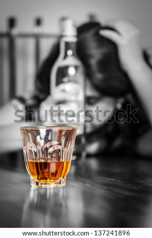 Alcoholism : Portrait of a lonely and desperate drunk hispanic woman (image focused on her drink) - stock photo