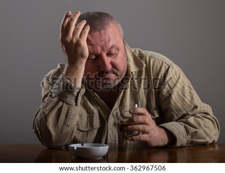 Alcoholism: portrait of a lonely, desperate man drinking alcohol and smoking cigarette - stock photo