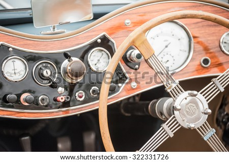 ALDERSHOT, UK - MAY 9: Closeup of a vintage British MG automobile dashboard with wooden steering wheel in Aldershot, UK on May 9, 2015
