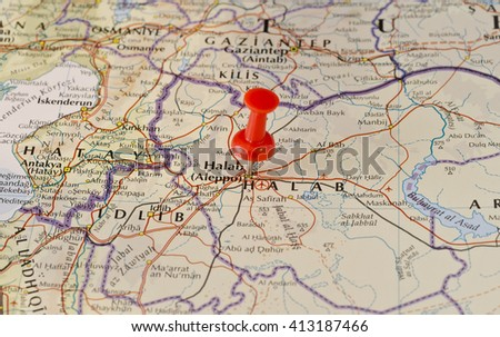Aleppo marked on map with red pushpin. Selective focus on the word Aleppo and the pushpin. Pin is in an angle. Midground is sharp while foreground and background is blurry. - stock photo