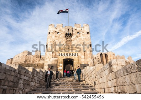 ALEPPO, SYRIA - DECEMBER 29, 2010: Visitors exit the gate of Aleppo (Halab) citadel at the end of 2010 shortly before start of Syrian civil war