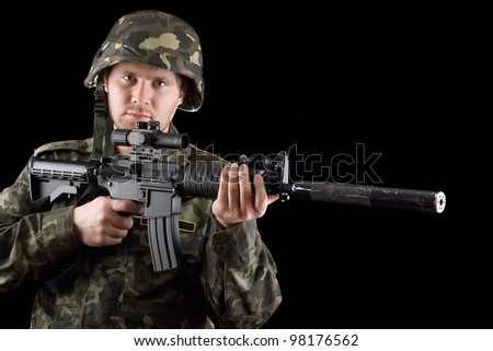 Alerted soldier holding m16 in studio. Closeup - stock photo