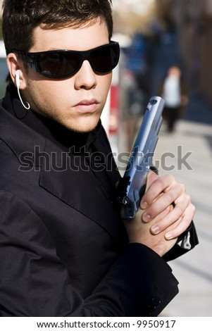 Alertness secret agent ready for action over urban background - stock photo