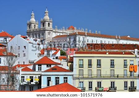 Alfama district typical houses and a view of Sao Vicente de Fora Monastery, old Lisbon (Portugal) - stock photo