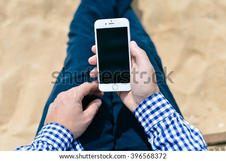 Algarve, Portugal - March 11, 2016: Person sitting and holding iPhone 6 mobile phone in hands. Top view closeup.  illustrative, editorial - stock photo