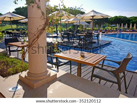 ALGARVE, PORTUGAL - OCTOBER 02, 2009: Table and chairs in outdoor cafe near resort swimming pool, Algarve, Portugal - stock photo