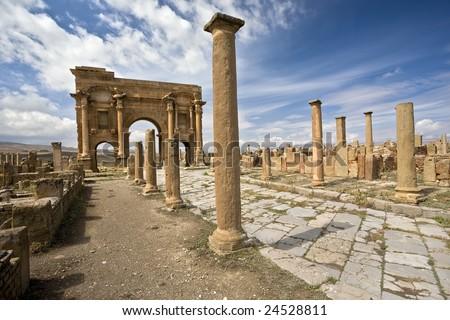 Algeria. Timgad (ancient Thamugadi or Thamugas). Decumanus Maximus street and surrounding colonnade terminated Trajan's Arch. - stock photo