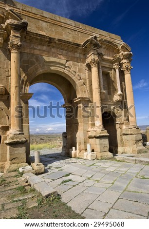 Algeria. Timgad (ancient Thamugadi or Thamugas). Triumphal arch, called Trajan's Arch (Corinthian order with three arches) and paving stones of Decumanus Maximus street - stock photo