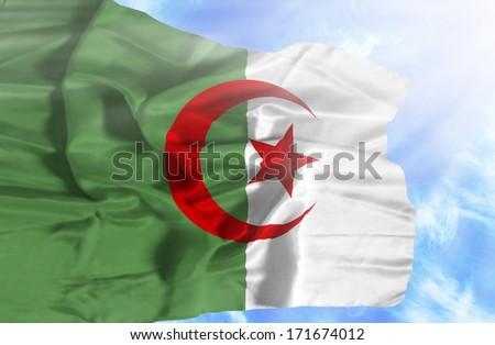 Algeria waving flag against blue sky with sunrays - stock photo