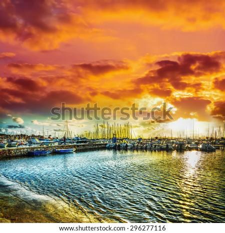 Alghero harbor under a dramatic sky at sunset - stock photo