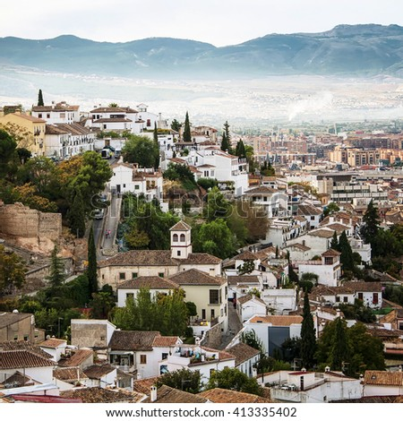 Alhambra palace located in Granada, Andalusia, Spain with aerial view at the city and mountains in the morning. It is a UNESCO World Heritage Site and a major touristic attraction. - stock photo