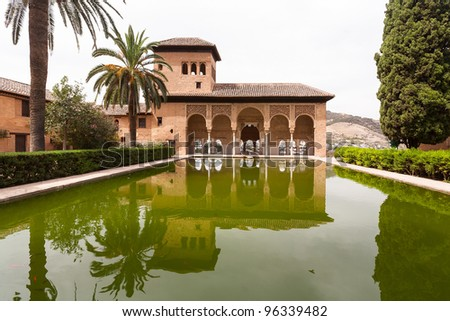 Alhambra palace of Granada reflected in water showing palm trees - stock photo